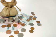 Money coins came out from brown money bag royalty free stock photography