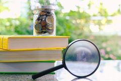 Money coins in the glass jar on the books and the magnifying glass on blurred natural green background. For financial and education concept royalty free stock photo