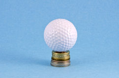 Money coins and golf ball on azure background Stock Photo