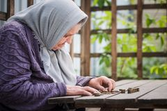 Money, coins, grandmother pensioner and the concept of subsistence minimum - old woman sad looking at the coins. Money, coins, retired grandmother and the stock photo