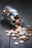 Money Coins Jar Savings. American coins spilling out of a glass jar on a wood background Royalty Free Stock Photo