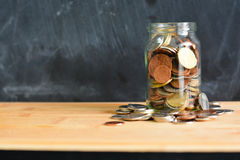 Money or coins in a jar suggesting home savings Stock Photos