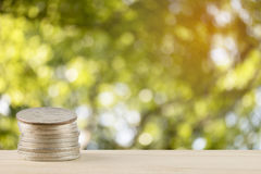 Money coins pile with abstract nature bokeh blur background, defocused leaves Stock Photography
