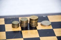 Money, coins sorted into piles. On a wooden background royalty free stock image