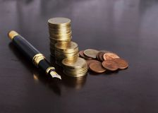 Money coins stack and Fountain Pen for Finance Concept stock images