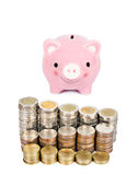 Money coins tower and pink piggybank. Stock Photo