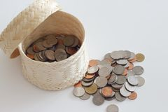 Money coins were put in the basket weave  on white backg. The Money coins were put in the basket weave  on white background Stock Photos