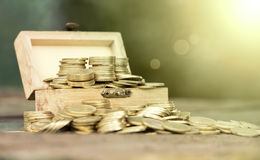 Money coins in a wooden box Royalty Free Stock Photo