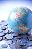 Money Coins World Globe. A world globe resting on a pile of mixed coins with a blue tone stock images