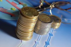 Money columns. Euro coins lying on colorful graphs royalty free stock photos