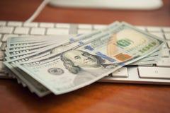 Money on computer keyboard royalty free stock image