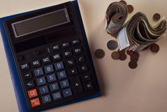 Money concept. Calculator with coins lie on the desktop, Royalty Free Stock Image