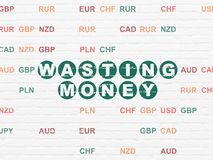 Money concept: Wasting Money on wall background. Money concept: Painted green text Wasting Money on White Brick wall background with Currency Stock Photography