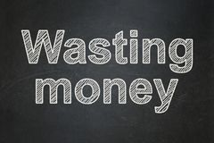 Money concept: Wasting Money on chalkboard background Royalty Free Stock Photography