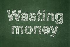 Money concept: Wasting Money on chalkboard background stock images