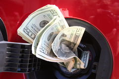 Money Consumer. Money coming out of a gas tank in a red car Stock Photos