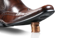 Money control. Shiny businessman shoe step on the stack of coins. Isolated royalty free stock images