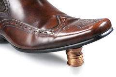 Money control - top view. Shiny businessman shoe, step on the stack of coins stock photos