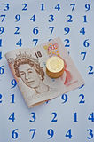 Money counts. Ten pound note and pound coins on a sheet covered by blue numbers making concept ' money counts Royalty Free Stock Photo