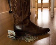 Money cowboy boot. One Hundred Dollar bills under the heal of a cowboy boot Stock Photos