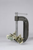 Money Crunch. A clamp squeezing dollar bills Royalty Free Stock Photo