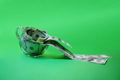 Money in cup. Dollars pouring out of the glass cup Royalty Free Stock Images