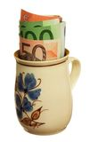 Money in a cup. Money in a painted cup on white background Royalty Free Stock Image