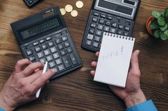 Money currency calculation. Calculator and blank note pad on office desk. Tax inspector or banker desk table background. Businessman male hands, notepad and Stock Photo