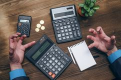 Money currency calculation. Calculator and blank note pad on office desk. Tax inspector or banker desk table background. Businessman male hands, notepad and Royalty Free Stock Image