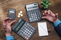 Money currency calculation. Calculator and blank note pad on office desk. Tax inspector or banker desk table background. Businessman male hands, notepad and Stock Photography