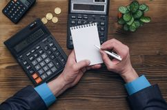 Money currency calculation. Calculator and blank note pad on office desk. Tax inspector or banker desk table background. Businessman male hands, notepad and Royalty Free Stock Images