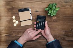 Money currency calculation. Calculator in businessman hands on office desk table background. Tax inspector or banker desk table background. Businessman male Royalty Free Stock Photos