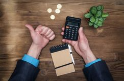 Money currency calculation. Calculator and thumb up gesture. Tax inspector or banker desk table background. Businessman male hands, notepad and calculator on Royalty Free Stock Photos