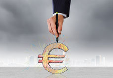 Money and currency. Close up of man hand drawing euro symbol Royalty Free Stock Photos