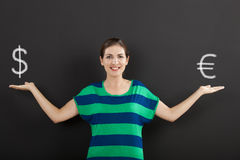 Money currency concept. Happy woman in front of a chalkboard ilustrating a concept about money currency Royalty Free Stock Photo