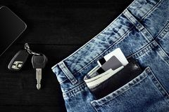 Money, Debit card and Credit card are in pocket of blue jean, Car keys, Smart on wooden background with copy space. One hundred dollar bills and cards in back Stock Photo