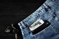 Money, Debit card and Credit card are in pocket of blue jean, Car keys on wooden background with copy space. One hundred dollar bills and cards in back of jean Royalty Free Stock Image