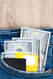 Money, Debit card and Credit card are in pocket of blue jean on. Wooden background with copy space. One hundred dollar bills and cards in back of jean pocket in Royalty Free Stock Photos