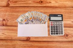 Money in denominations of 100 dollars in a white envelope and a calculator on a wooden table. View from above. royalty free stock image