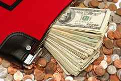 Money deposit bag. Close up of a red money bag on coins with an extruding pile of bank notes Royalty Free Stock Photos