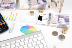 Money on desk witch chart. British pound sterling bank notes on desk with financial chart stock image