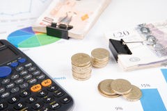 Money on desk witch chart. British pound sterling bank notes on desk with financial chart stock photo