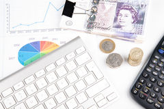 Money on desk witch chart. British pound sterling bank notes on desk with financial chart royalty free stock photos