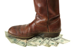 Money Devalued is Trod Under Foot. A boot stomps on money that is devalued and more worthless on white stock image