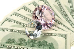 Money and diamonds. Pink and white diamond laying on dollars, isolated Stock Photos
