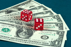 Money and  dice. Red dice  lying on the dollar denominations spread out by a fan Royalty Free Stock Photo