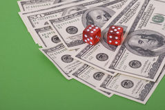Money and dice. Lot ot paper money, dollars, and red dice Stock Photography