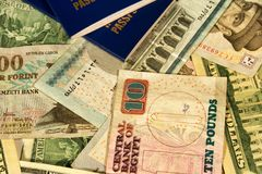 Money from different countries in the pile and two passports fro. M above. The concept of preparation for travel. Selective focus. Close-up Royalty Free Stock Images