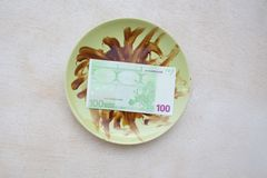 Money on a dirty plate Stock Photo