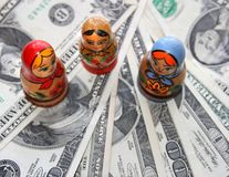 Money and doll. A pile of dollars and three russian dolls Royalty Free Stock Photo